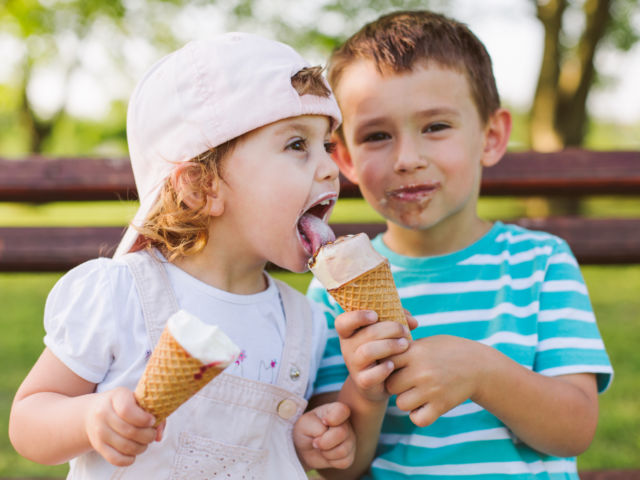 boy share ice cream with his sister